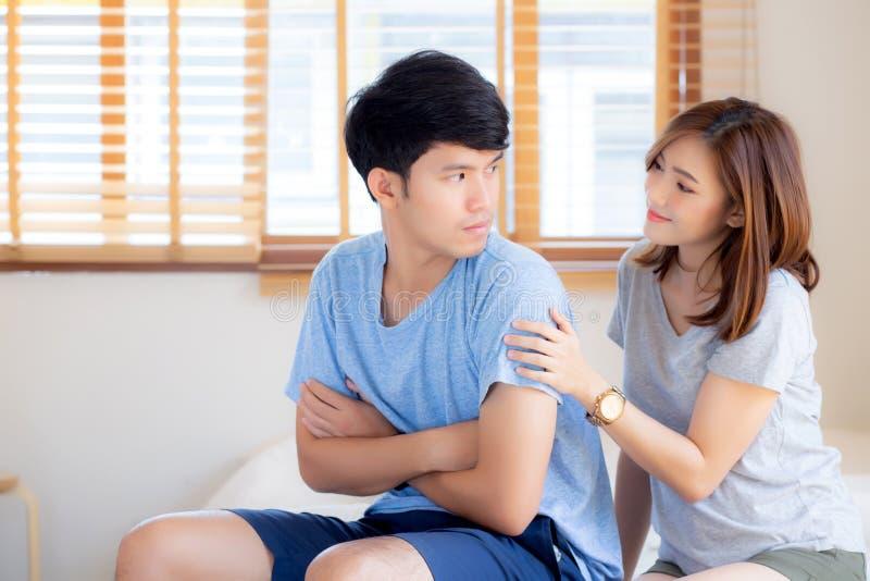 Młoda azjatykcia para kobieta i problem pyta wybacza i zmartwiony z mężczyzny czuć gniewny przy sypialnią zdjęcia stock
