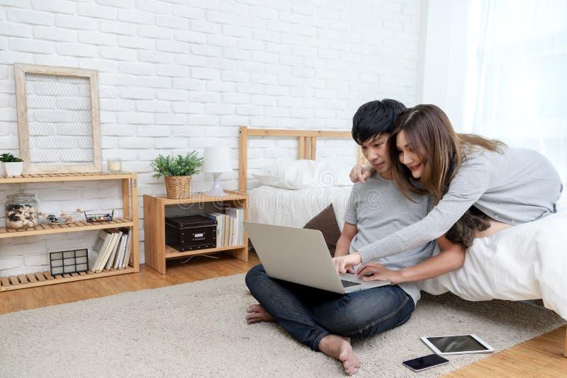 Młoda azjatykcia para patrzeje laptop szukać dla planu podróży, książkowego pokoju hotelowego, zakupu bilet, zakup podróży ubezpi zdjęcia royalty free