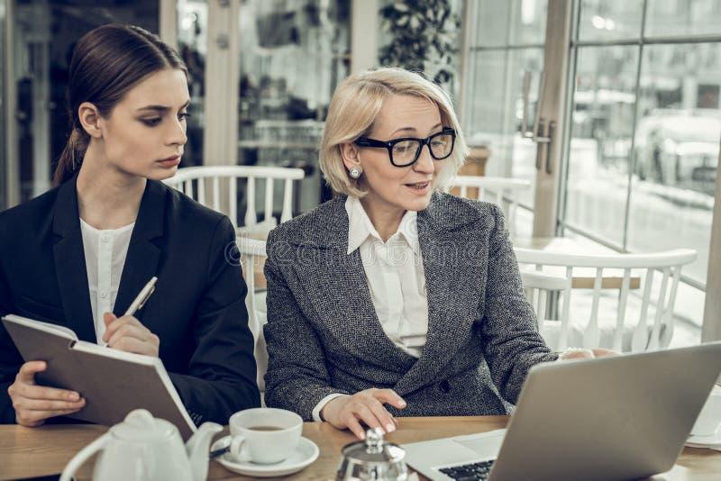 Młoda baczna sekretarka słucha jej pomyślny żeński szef zdjęcia royalty free