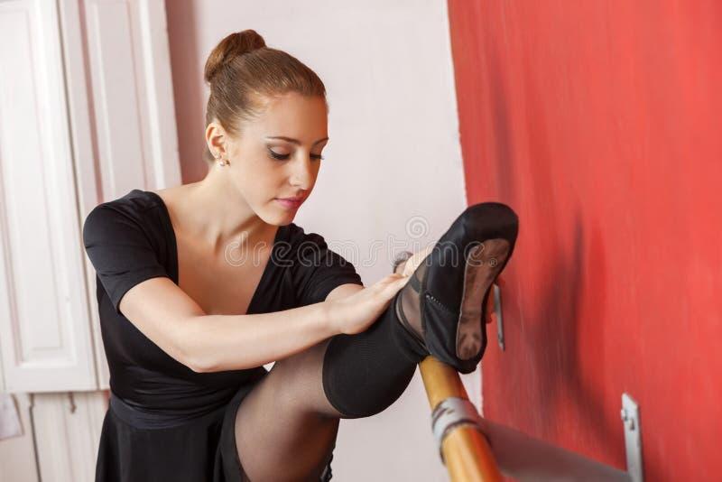 Młoda balerina Rozciąga Jej nogę Przy Barre fotografia royalty free