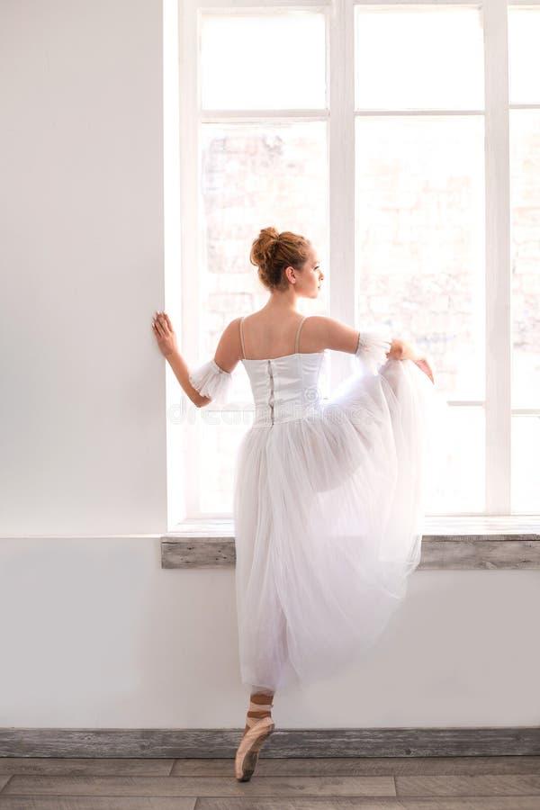 Młoda balerina rozciąga na taniec sali zdjęcia royalty free
