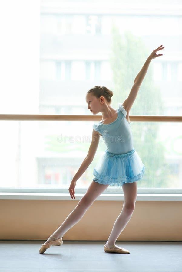 Młoda balerina w błękita smokingowy ćwiczyć w studiu zdjęcia stock