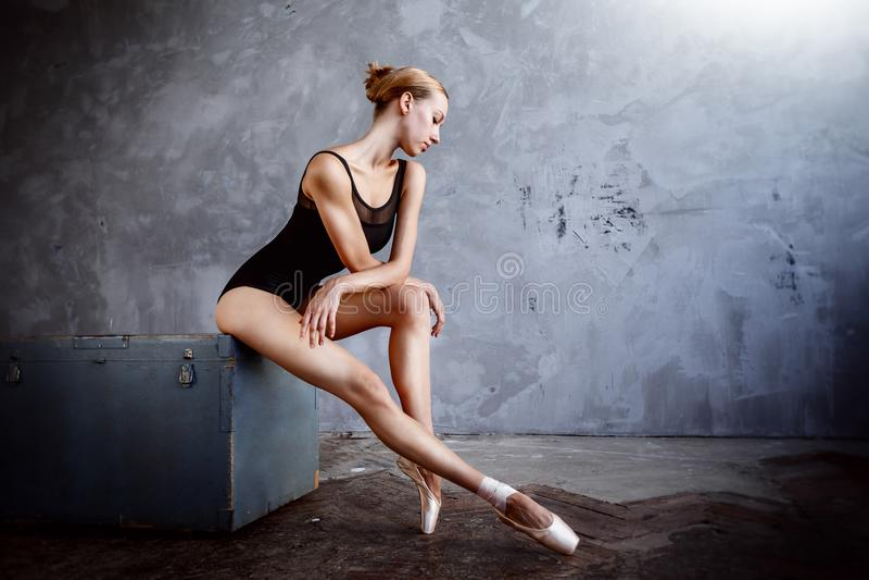 Młoda balerina w czarnym tana kostiumu pozuje w loft studiu zdjęcia stock