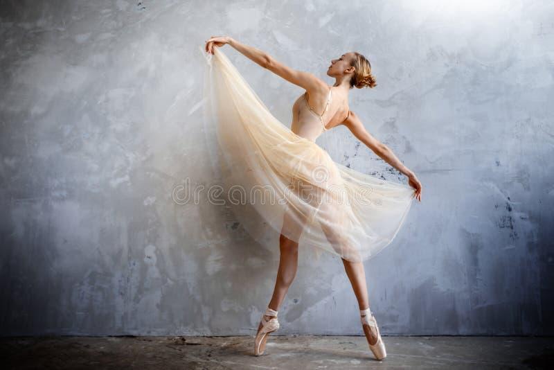 Młoda balerina w złotym barwionym dancingowym kostiumu pozuje w loft studiu zdjęcie stock