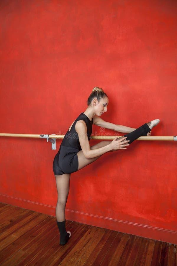 Młoda balerina Z nogą Na barze W studiu obrazy royalty free