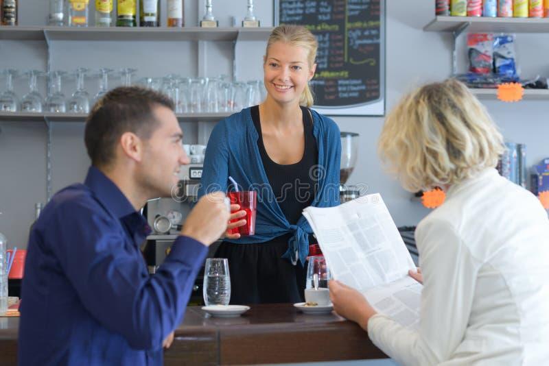 Młoda barista porci kawa dobierać się w kawiarni obrazy stock