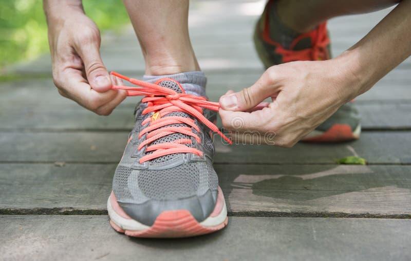 Młoda biała kobieta wiąże działających buty obraz stock
