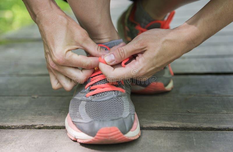 Młoda biała kobieta wiąże koronki na jej działających butach zdjęcia royalty free