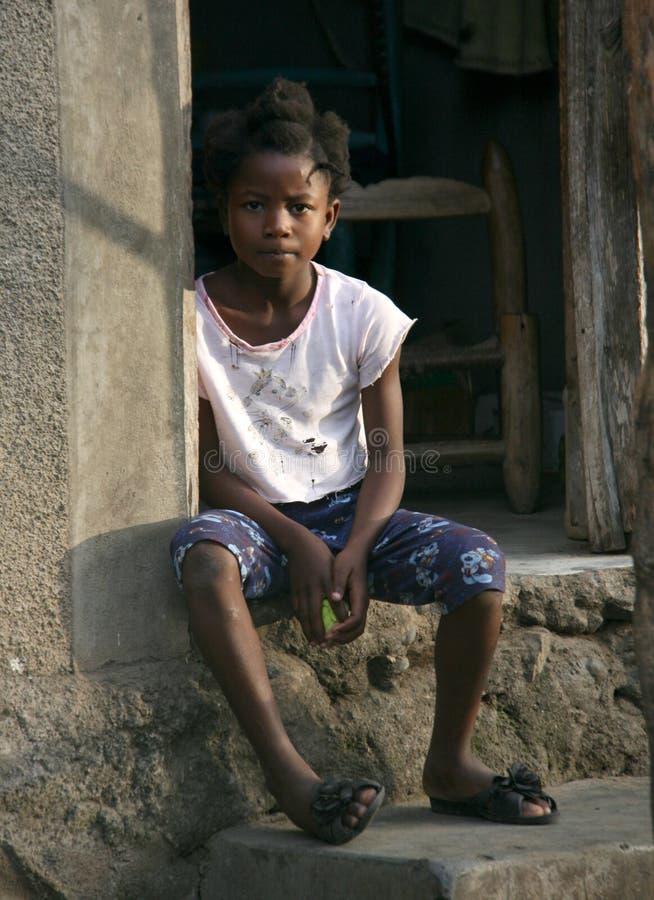 Młoda biedna Haitańska dziewczyna siedzi na zewnątrz jej wioski przestrzegającej w wiejskim Haiti zdjęcie royalty free