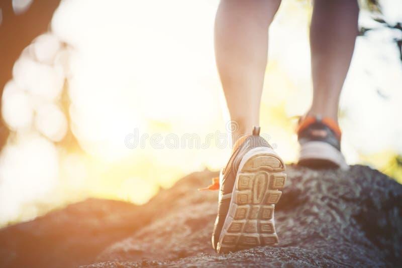 Młoda biegacz kobieta iść na piechotę zakończenie podczas bieg przez skałę, obrazy stock