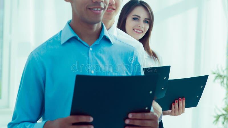 Młoda biznes drużyna stoi w biurze z dokumentami zdjęcia stock