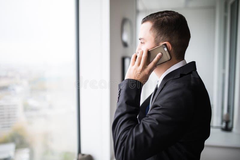 młoda biznesmen pozycja obok wielkich okno jego najwyższego piętra biuro, patrzeje widok miasto podczas gdy opowiadający na cześć zdjęcia royalty free