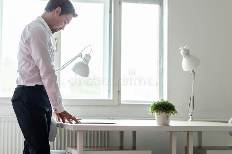 Młoda biznesmen pozycja przy jego biurkiem czyta kontrakt zdjęcie stock