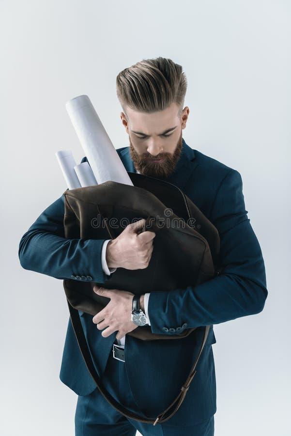 Młoda biznesmena mienia torba z staczającymi się projektami na popielatym zdjęcie royalty free