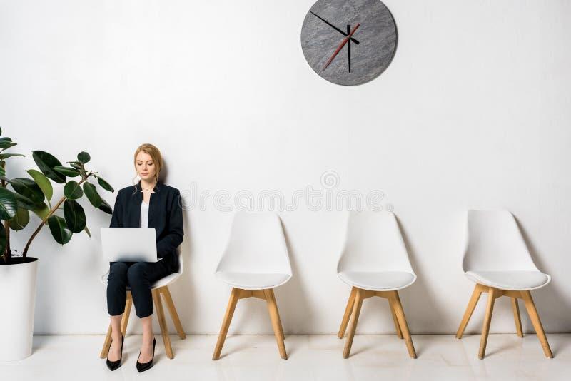 mÅ'oda biznesmenka korzystajÄ…ca z laptopa podczas siedzenia i oczekiwania zdjęcie royalty free