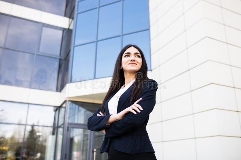 Młoda biznesowa dziewczyna przed nowożytnymi biznesowymi biurami ześrodkowywa zdjęcie stock