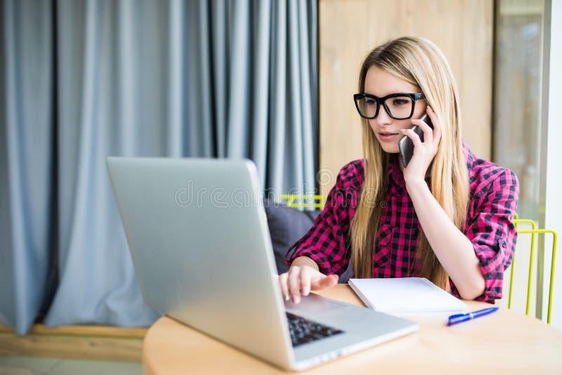 Młoda biznesowa kobieta, dzwoni przy biurowym, martwił się wyrażenie na jej twarzy patrzeje laptop który jest przed ona fotografia royalty free