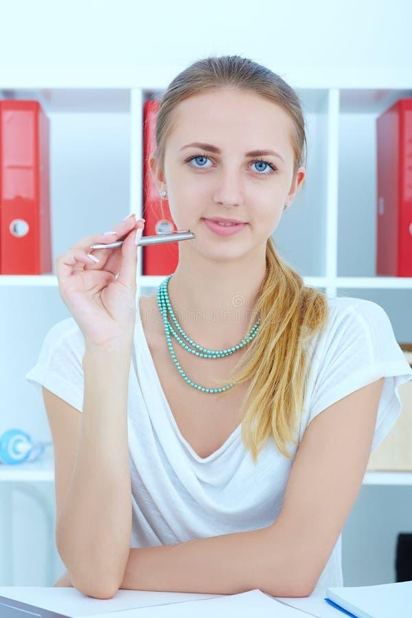 Młoda biznesowa kobieta lub uczeń pracuje przy biurem z jej papierkową robotą obraz stock