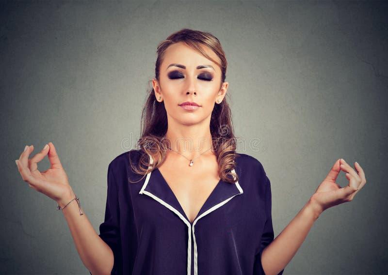 Młoda biznesowa kobieta medytuje z oczami zamykającymi zdjęcie stock