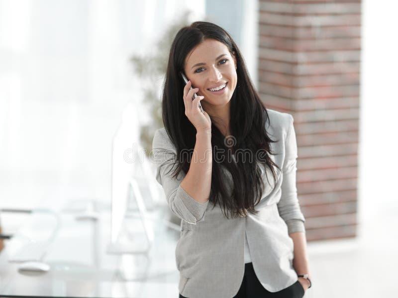 Młoda biznesowa kobieta opowiada na smartphone zdjęcie royalty free