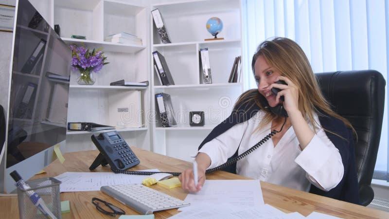 Młoda biznesowa kobieta opowiada na telefonie komórkowym i robi notatkom w notatniku podczas gdy siedzący przy stołem w biurze zdjęcia stock