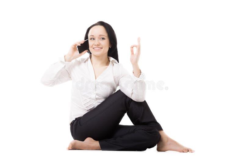 Młoda biznesowa kobieta opowiada na telefonie komórkowym na whi w joga pozie zdjęcie royalty free