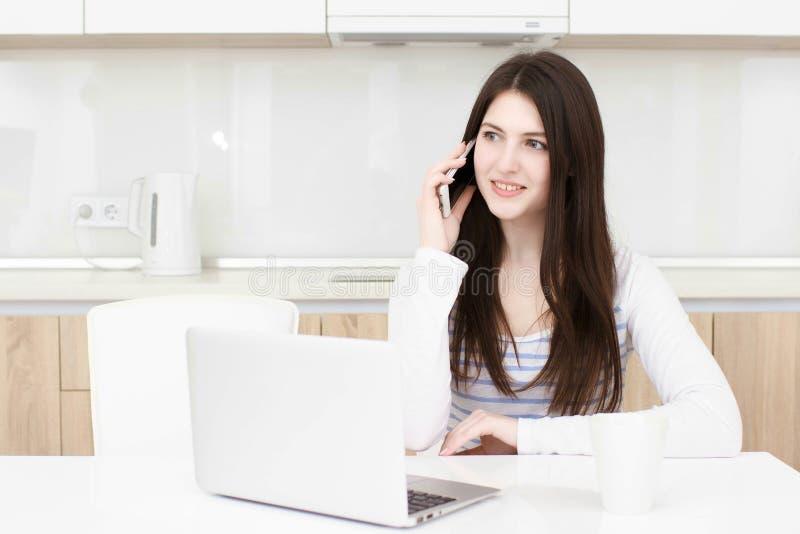 Młoda biznesowa kobieta opowiada na telefonie podczas gdy siedzący przy stołem obraz royalty free