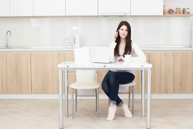 Młoda biznesowa kobieta opowiada na telefonie podczas gdy siedzący przy stołem obrazy stock