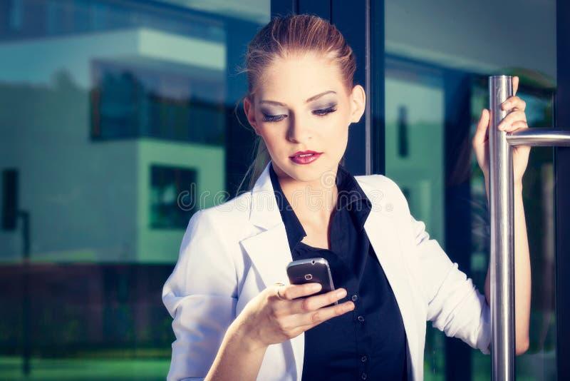 Młoda biznesowa kobieta opowiada telefon komórkowego na ulicie przeciw budynkowi zdjęcie royalty free