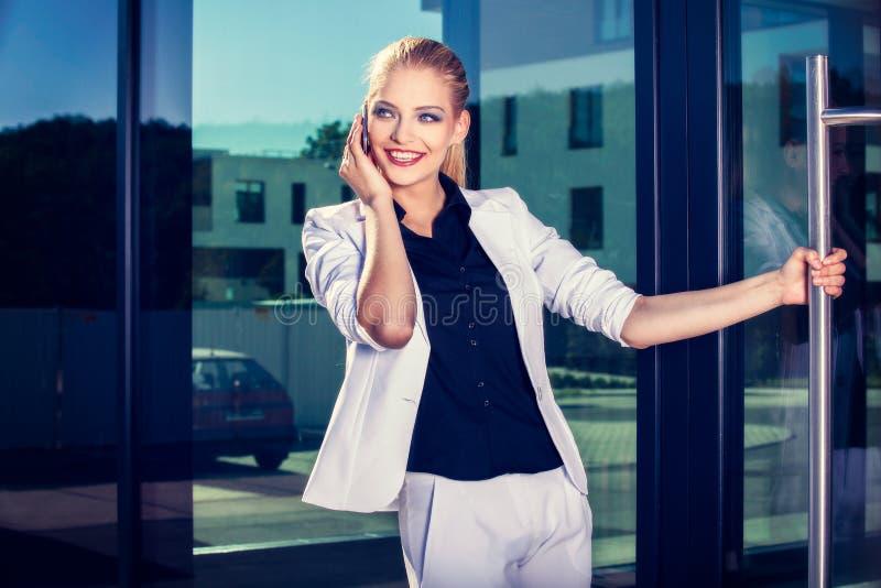 Młoda biznesowa kobieta opowiada telefon komórkowego na ulicie przeciw budynkowi obraz royalty free
