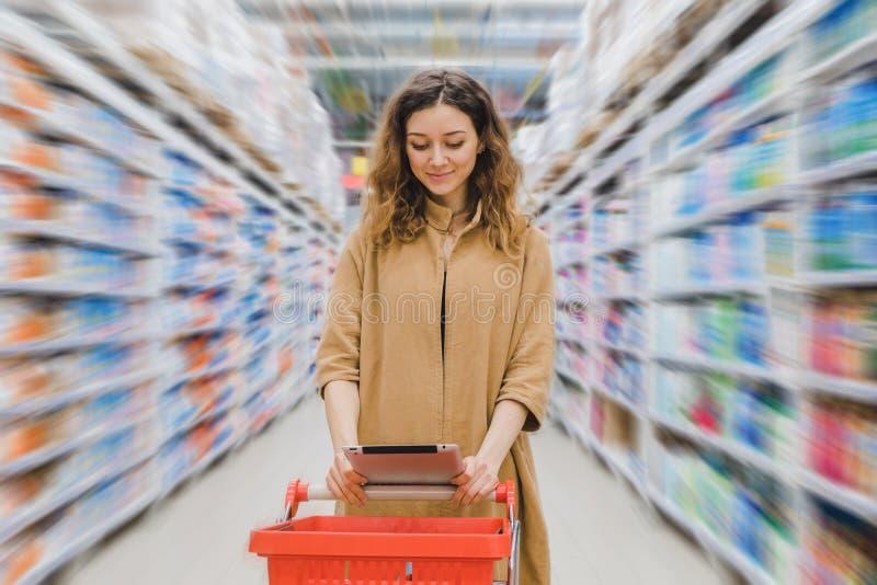 Młoda biznesowa kobieta patrzeje w pastylkę w supermarkecie między półkami z sklepu spożywczego wózek na zakupy obrazy stock