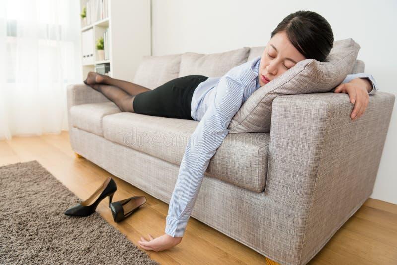 Młoda biznesowa kobieta po praca łgarskiego puszka na kanapie fotografia royalty free