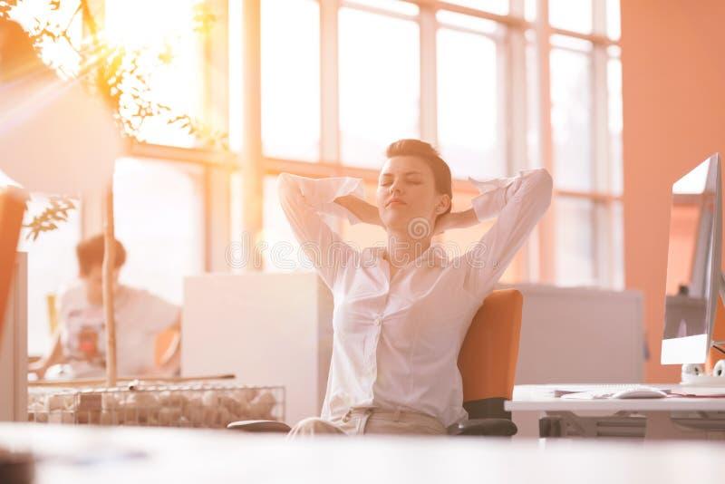 Młoda biznesowa kobieta relaksuje przy miejscem pracy zdjęcie stock