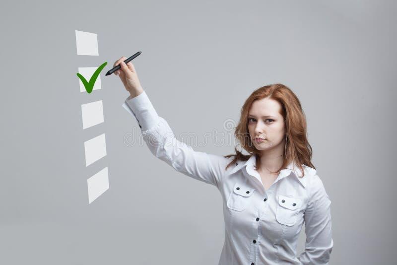 Młoda biznesowa kobieta sprawdza na listy kontrolnej pudełku Szary tło zdjęcia royalty free