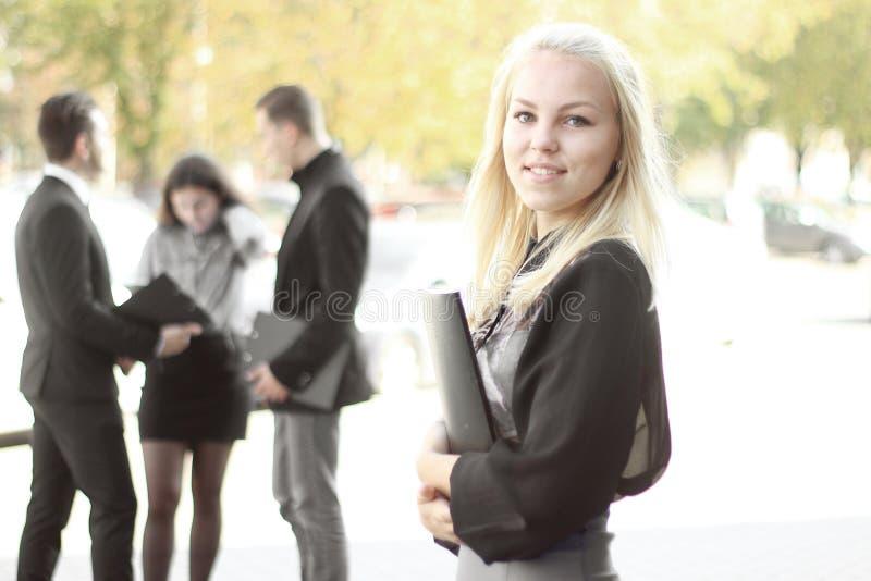 Młoda biznesowa kobieta stoi outdoors blisko biura z schowkiem zdjęcia stock