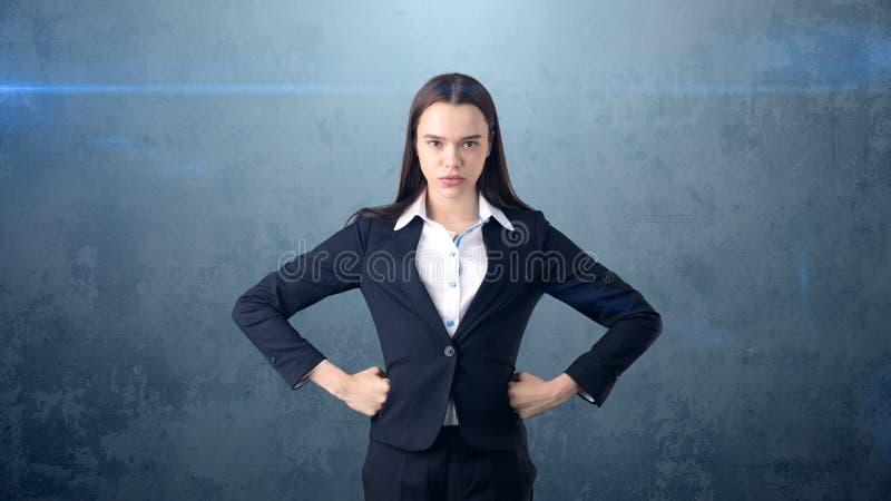 Młoda biznesowa kobieta trzyma jej ręki na biodrach w czarnym kostiumu i białej koszula stoi, Długowłosa dziewczyna jest poważna obrazy stock