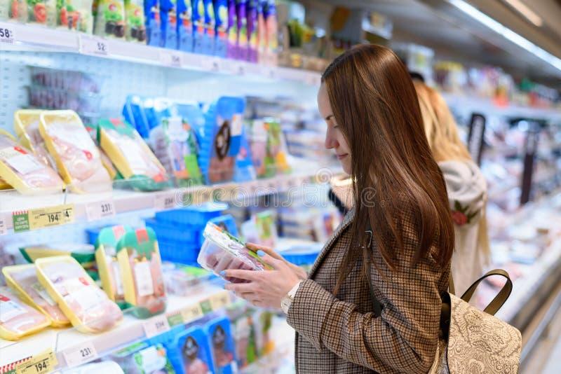 Młoda biznesowa kobieta trzyma pakunek Turcja w kurtce w sklepie, czyta skład obrazy stock