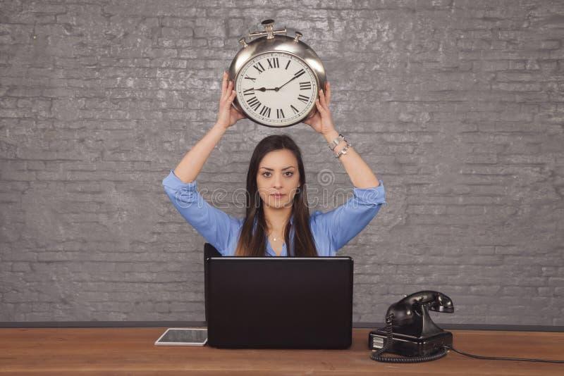 Młoda biznesowa kobieta trzyma zegar nad jej głową, pojęcie b zdjęcie royalty free