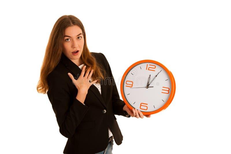 Młoda biznesowa kobieta trzyma zegar odizolowywający nad bielem - czas obraz royalty free