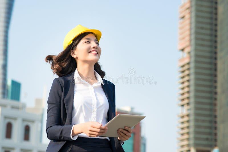 Młoda biznesowa kobieta używa pastylkę w ulicie z biurowymi bu obraz stock