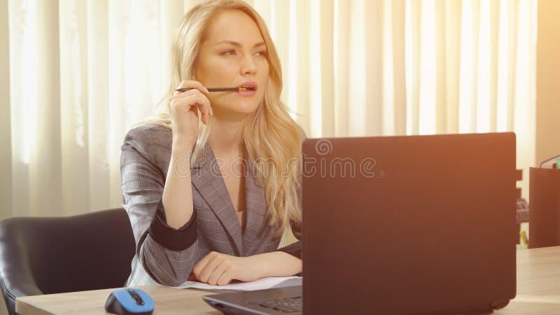 Młoda biznesowa kobieta w kostiumu pracuje przy komputerem w biurze zdjęcie stock