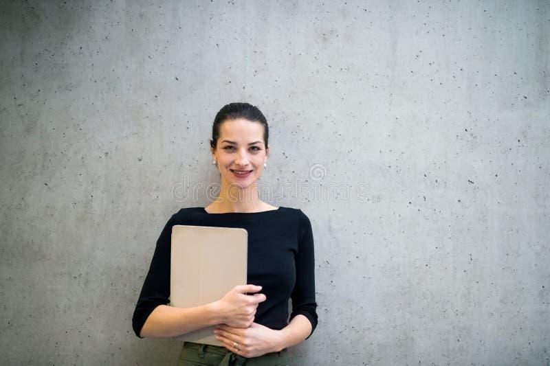 M?oda biznesowa kobieta z schowek pozycj? przeciw betonowej ?cianie w biurze zdjęcia stock
