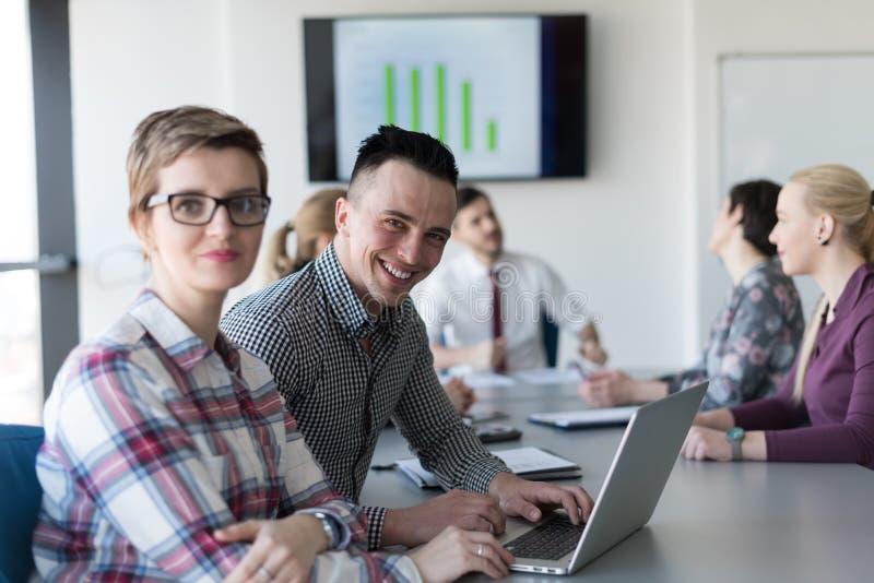 Młoda biznesowa para pracuje na laptopie, biznesmen grupa dalej obrazy royalty free