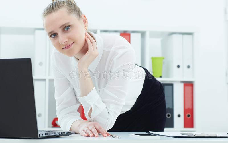 Młoda bizneswoman pozycja obok stołu z laptopem Biznes, wekslowy rynek, oferta pracy, analityka bada zdjęcie stock