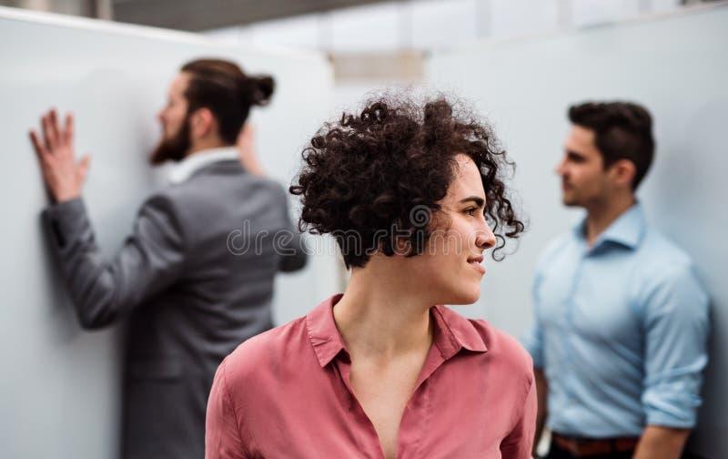 Młoda bizneswoman pozycja w biurze, koledzy w tle zdjęcia stock