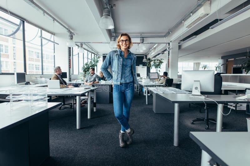 Młoda bizneswoman pozycja w biurze z kolegami obrazy royalty free