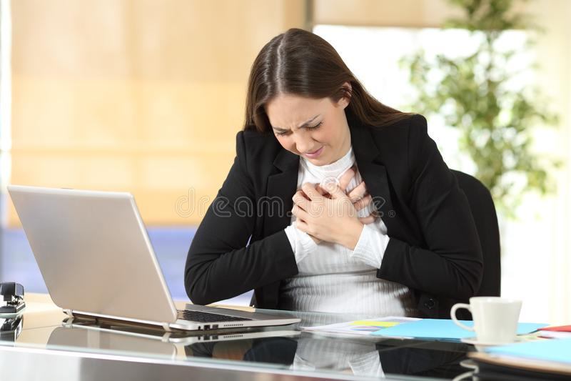 Młoda bizneswomanu cierpienia klatki piersiowej obolałość przy biurem obrazy royalty free