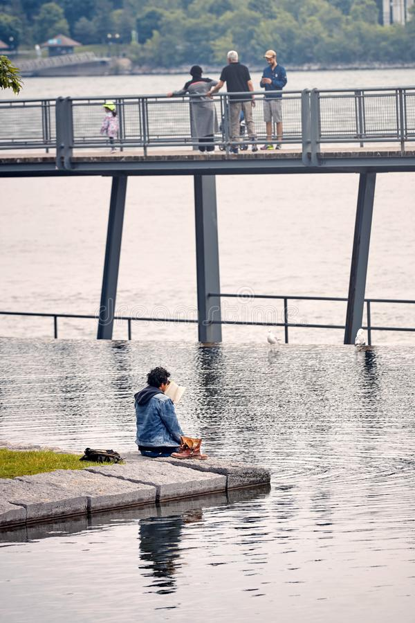 Młoda bliskowschodnia samiec czyta książkowego obsiadanie rzeką fotografia royalty free