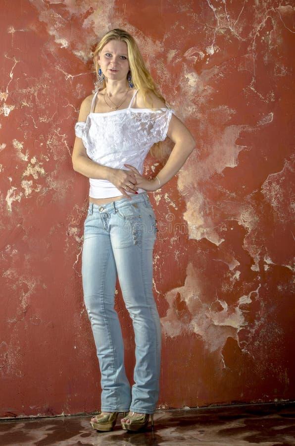 Młoda blond dziewczyna w cajgach i białym pulowerze obraz stock