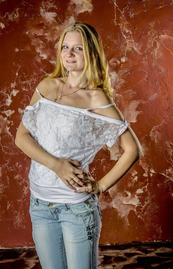 Młoda blond dziewczyna w cajgach i białym pulowerze obraz royalty free